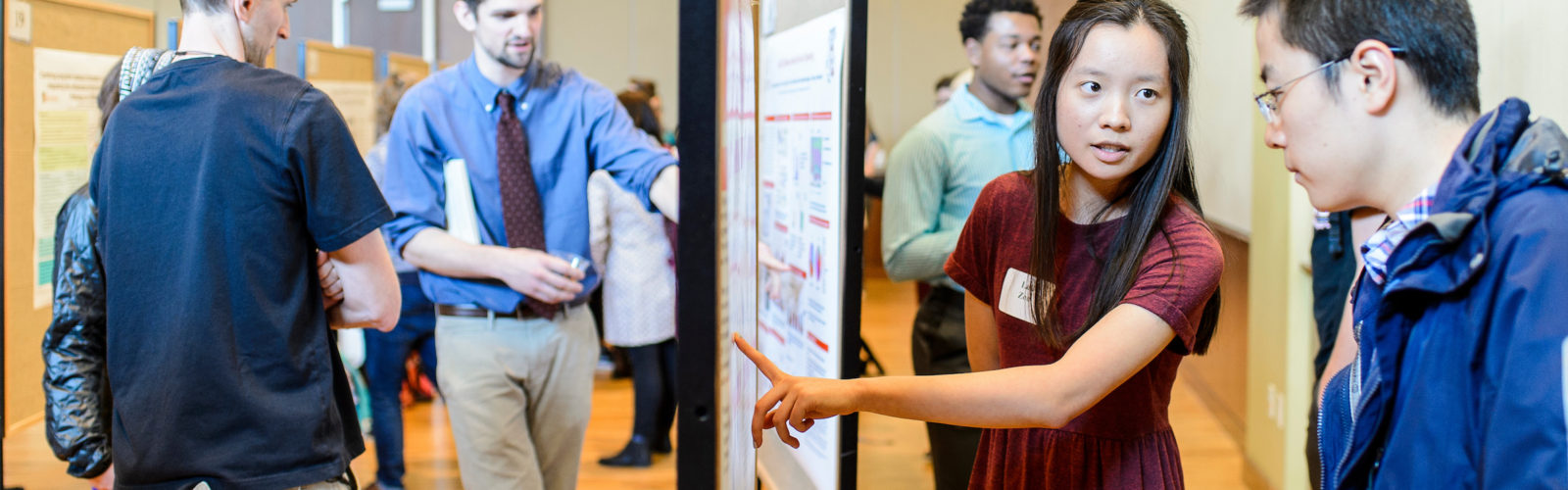 Students use their poster boards to describe their research to visitors at the annual Undergraduate Symposium
